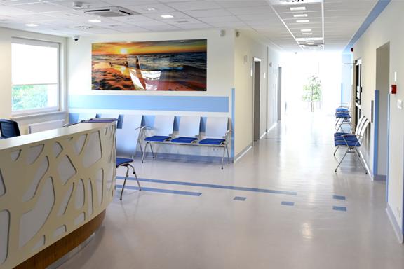 Wyposażenie poradni przy ul. Klaudyny 26 B składające się z lady rejestracji, krzeseł dla pacjentów oraz obrazu na ścianie, ukazującego zachód słońca